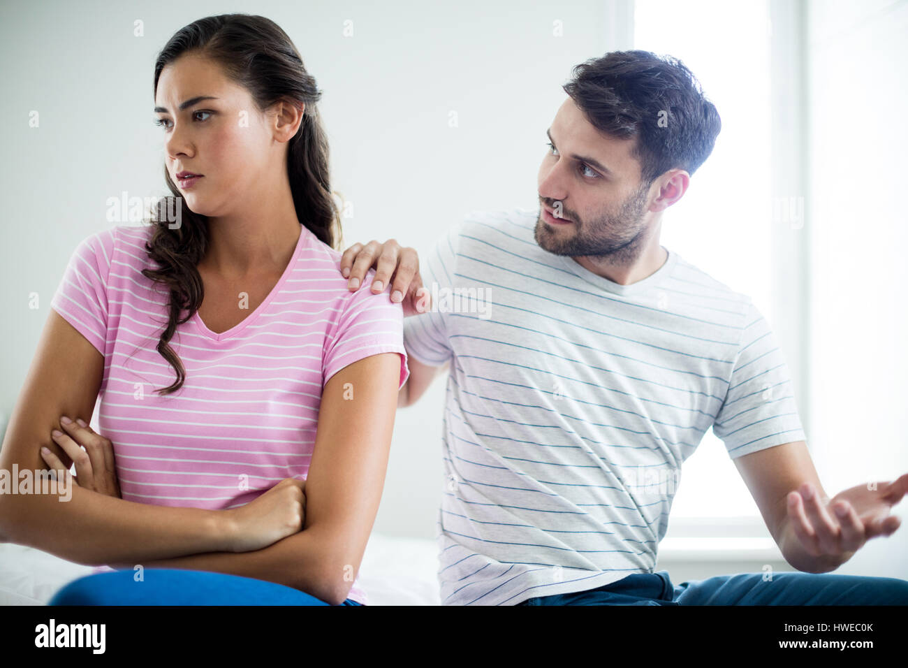Couple arguing with each other in bedroom at home - Stock Image