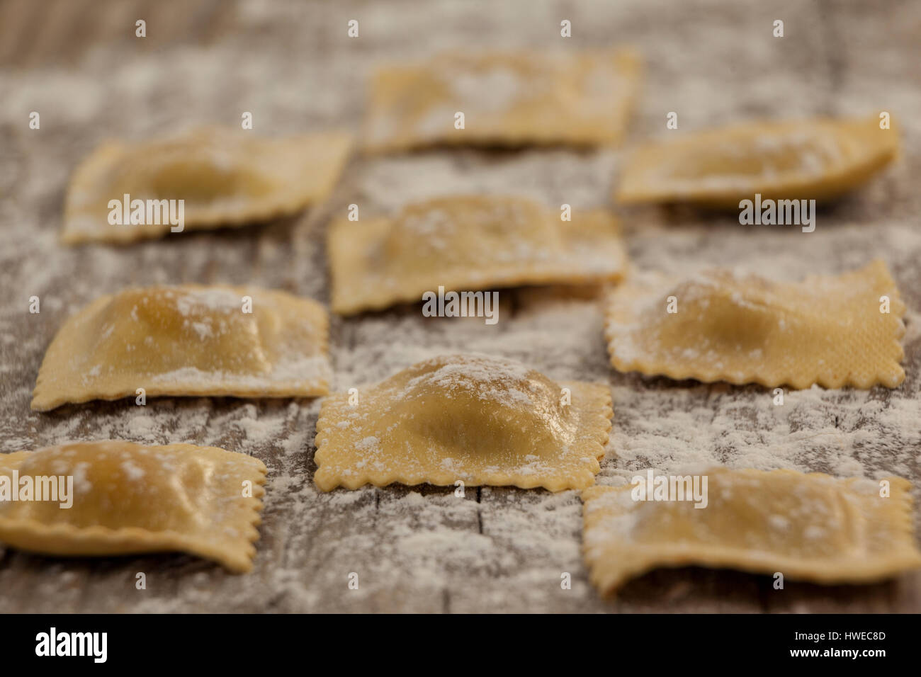 Close-up of ravioli pasta dusted with floor on wooden background - Stock Image