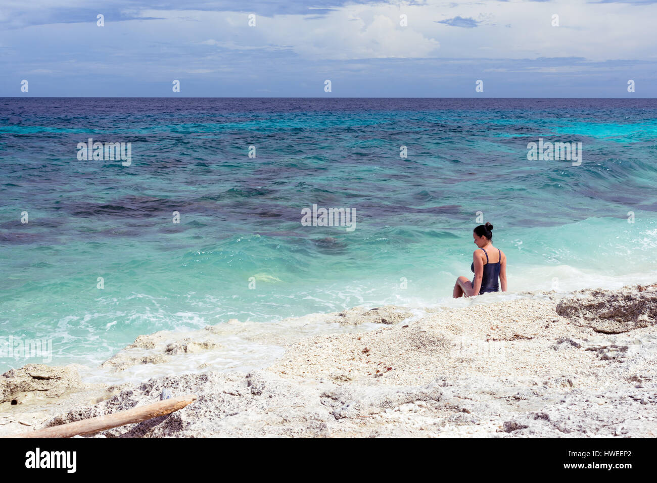 A beautiful young woman in a bathing suit sat on an empty coral rock beach looking out to a deep blue sea. - Stock Image