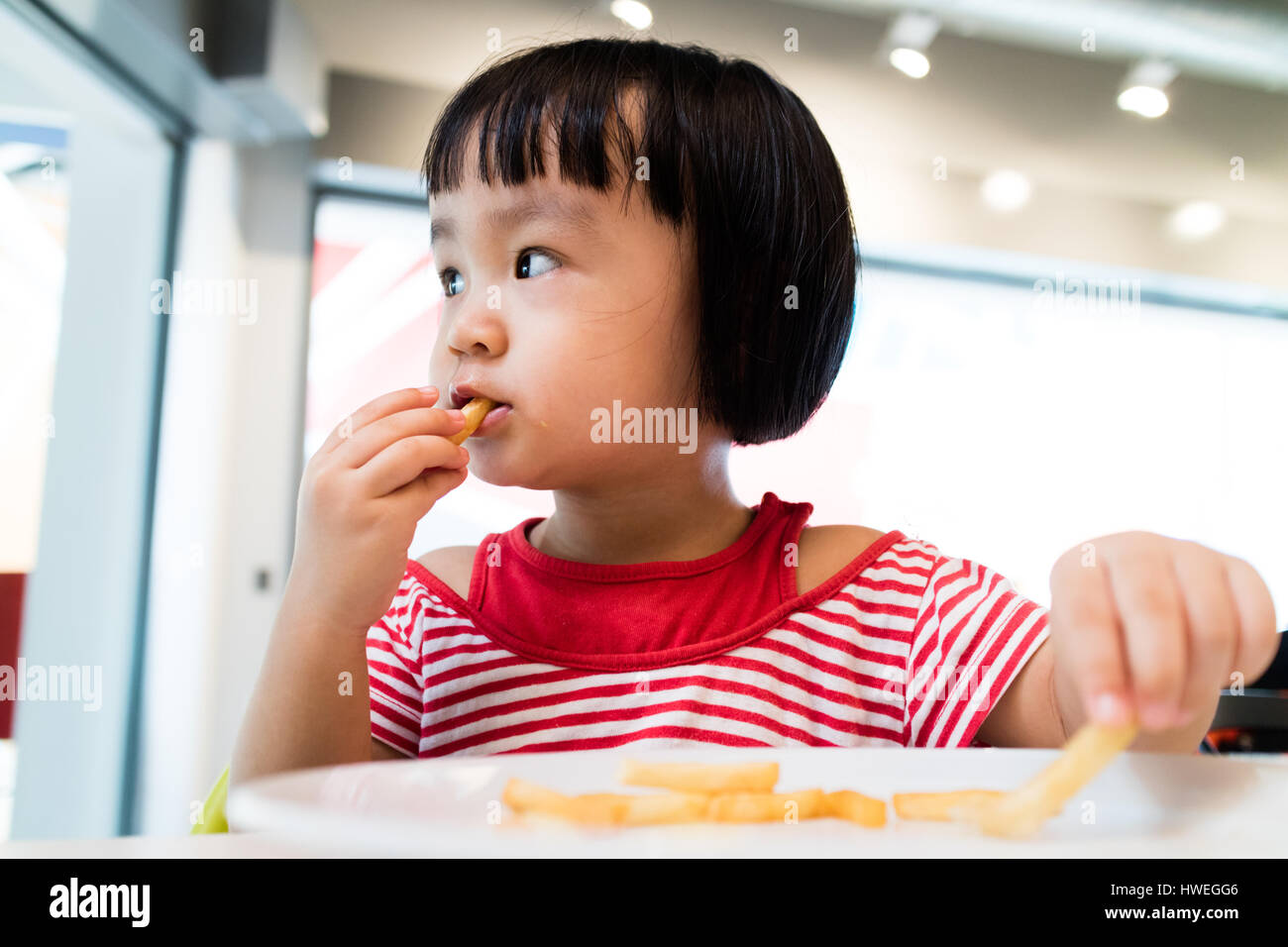 Asian Chinese little girl eating french fries at restaurant. - Stock Image
