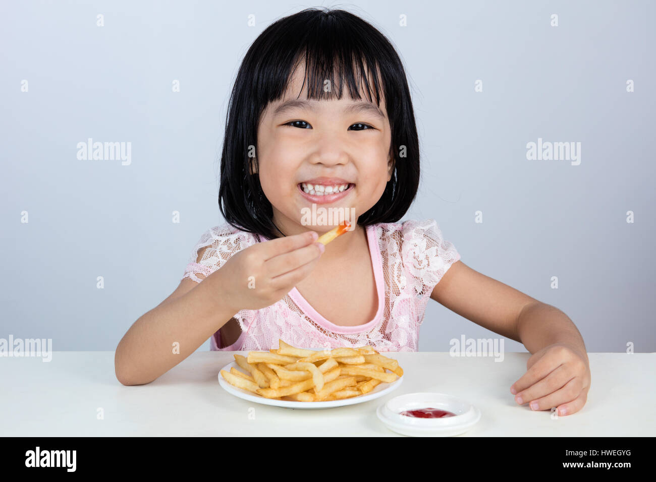 Happy Asian Chinese little girl Eating French Fries at indoor isolated clean background. - Stock Image