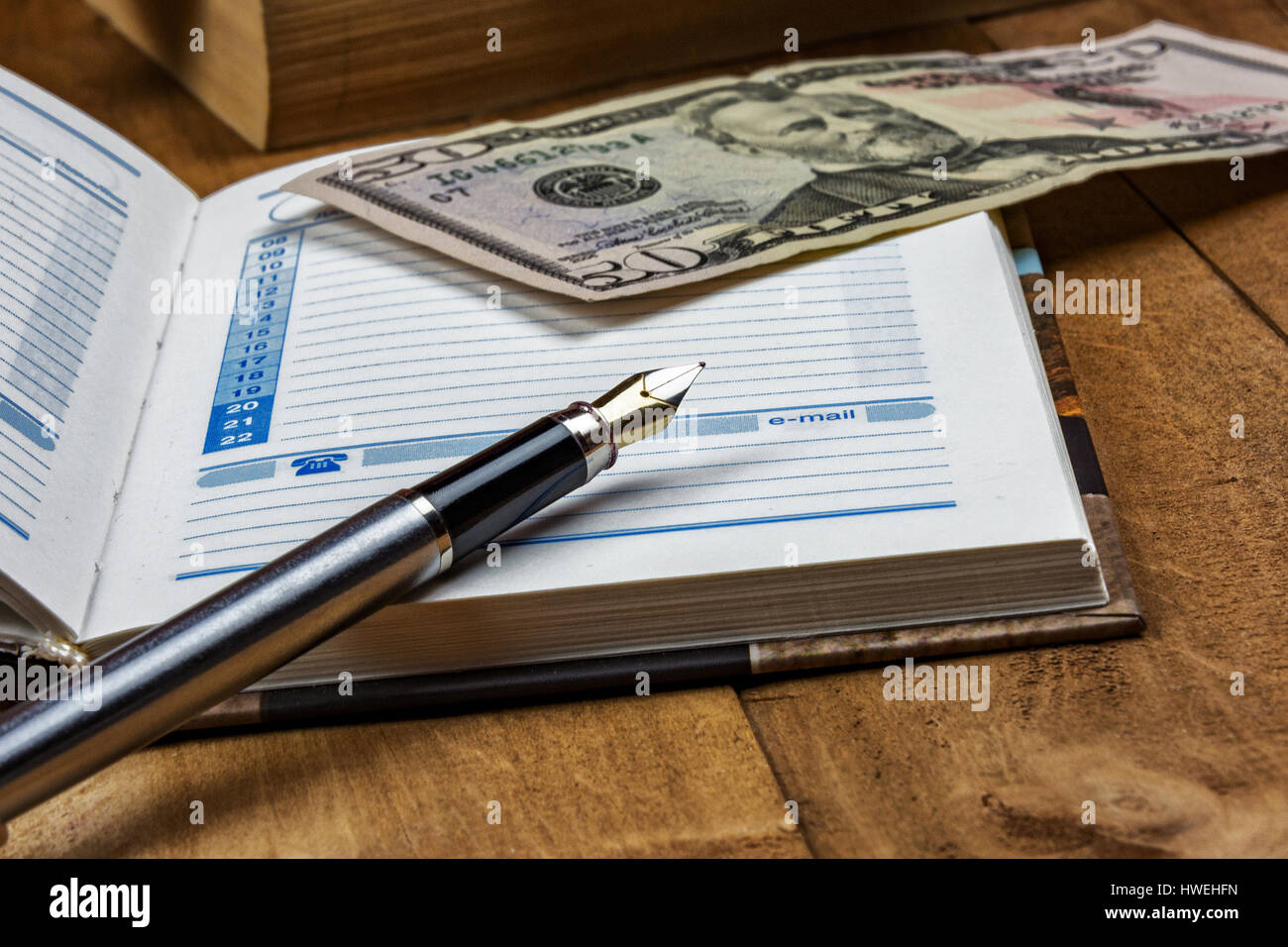 On the wooden surface is an open diary, a fountain pen and a money bill - Stock Image