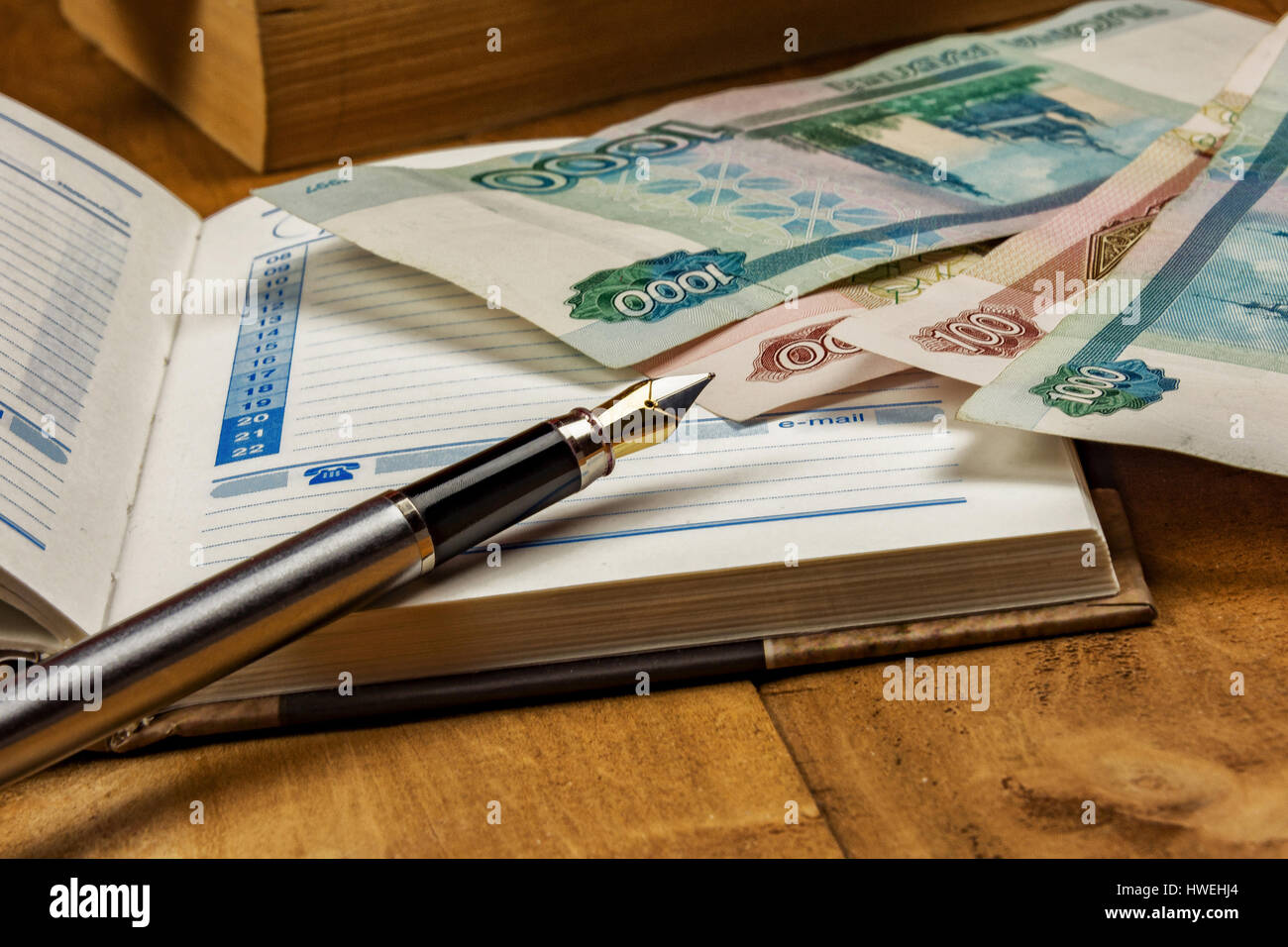 On the wooden surface is an open diary, a few bills and a fountain pen - Stock Image