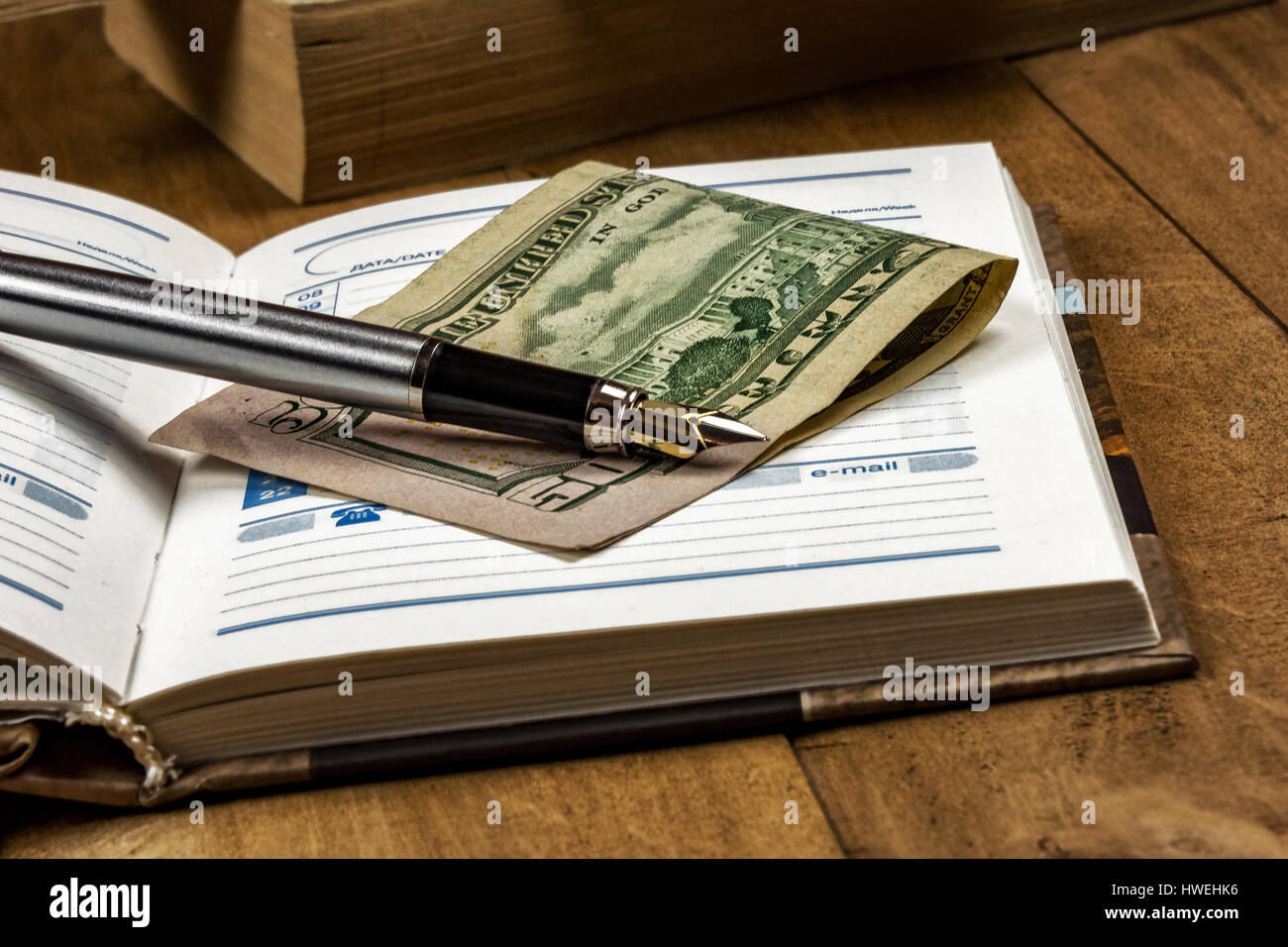 On the wooden surface is an open diary, a money note and fountain pen - Stock Image