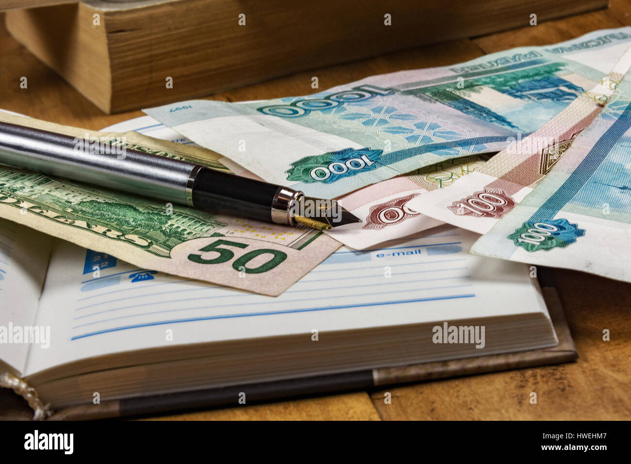On the wooden surface is an open diary, money bills and fountain pen - Stock Image