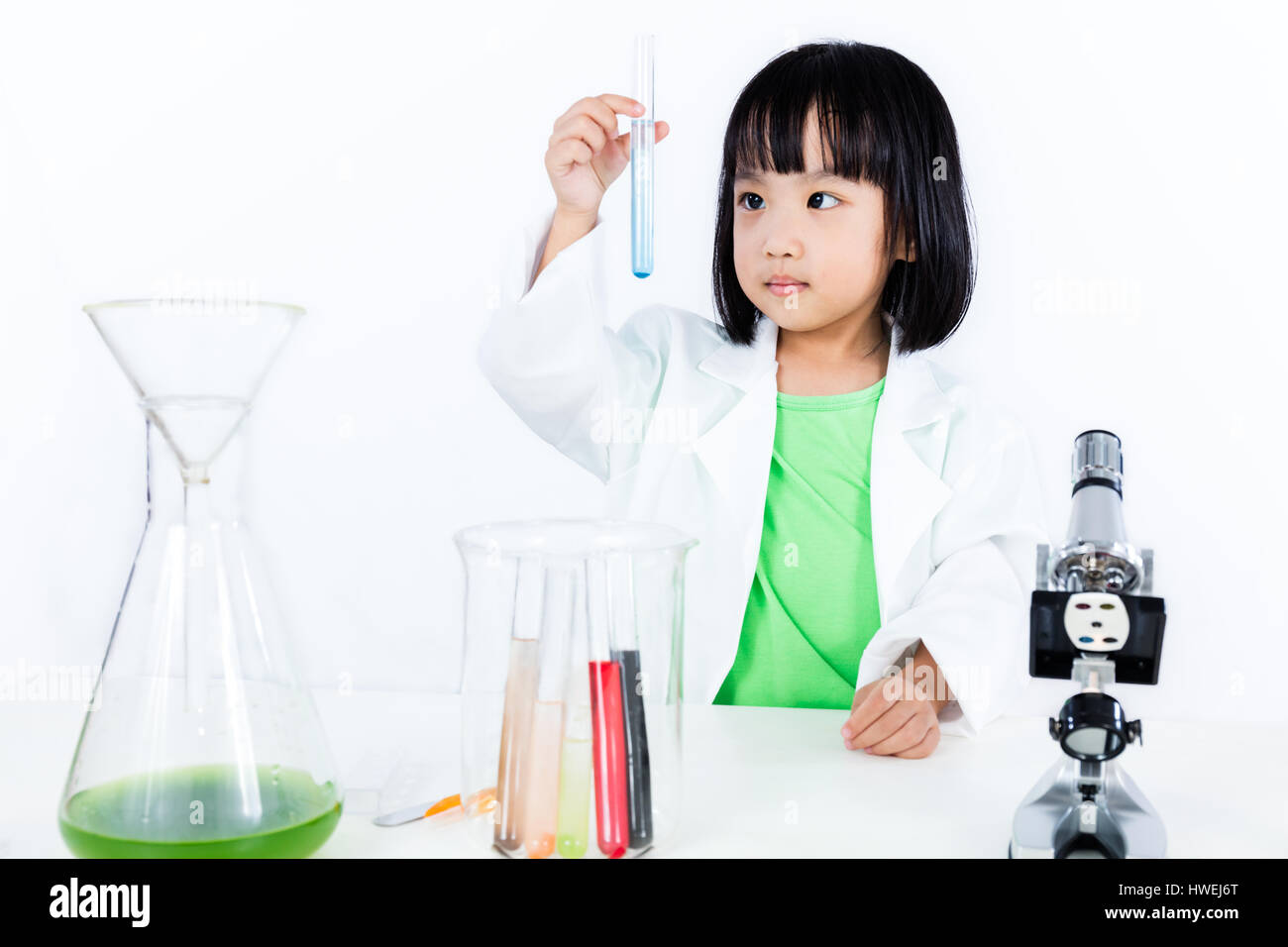 Asian Chinese Little Girl Examining Test Tube With Uniform in isolated  white background. - Stock