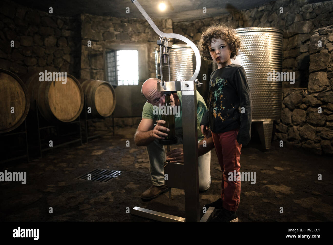 Boy with winemaker corking wine bottle in cellar - Stock Image