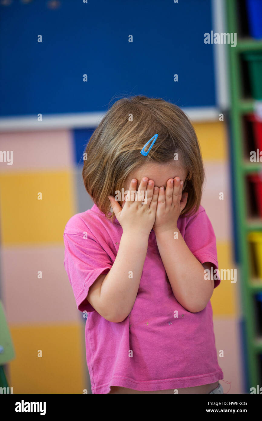 Preschool girl covering her eyes with hands in classroom - Stock Image