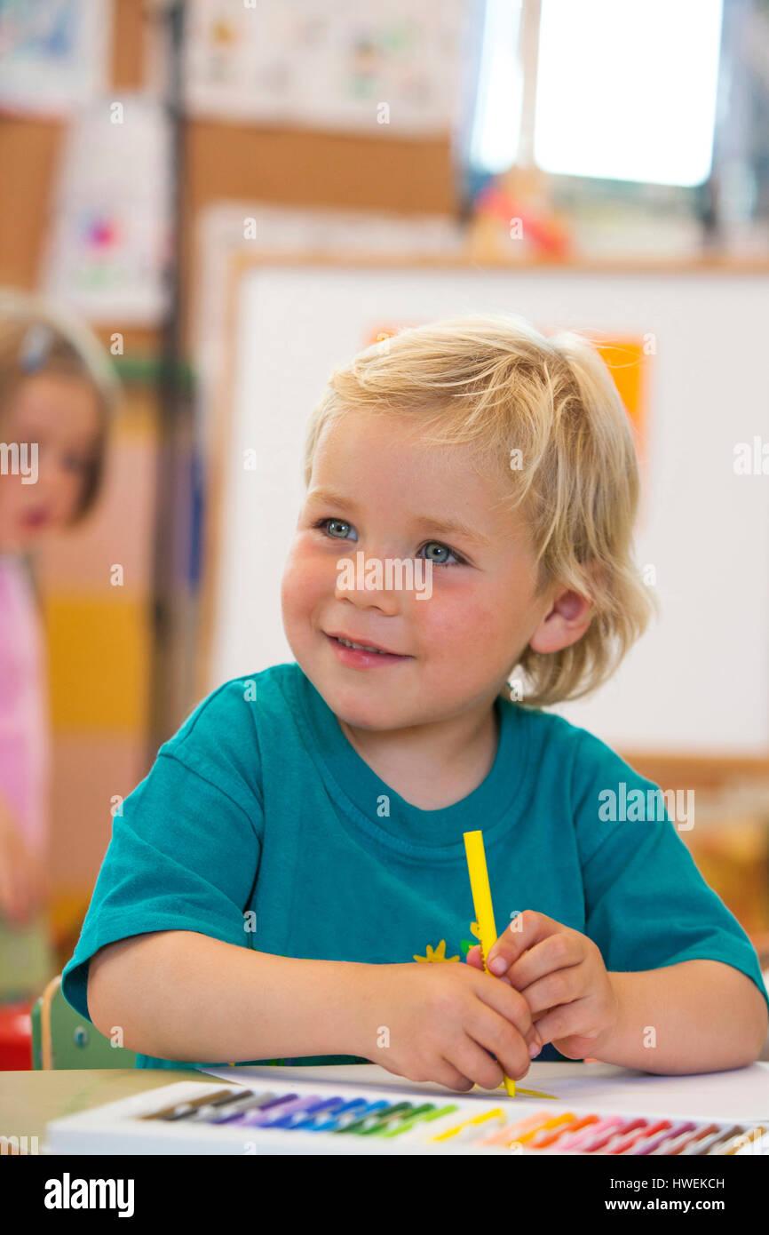 Preschool boy with colouring pen in classroom - Stock Image