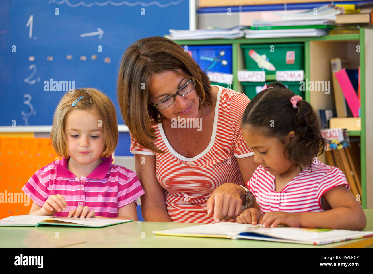 Preschool girls and teacher reading storybook in classroom - Stock Image