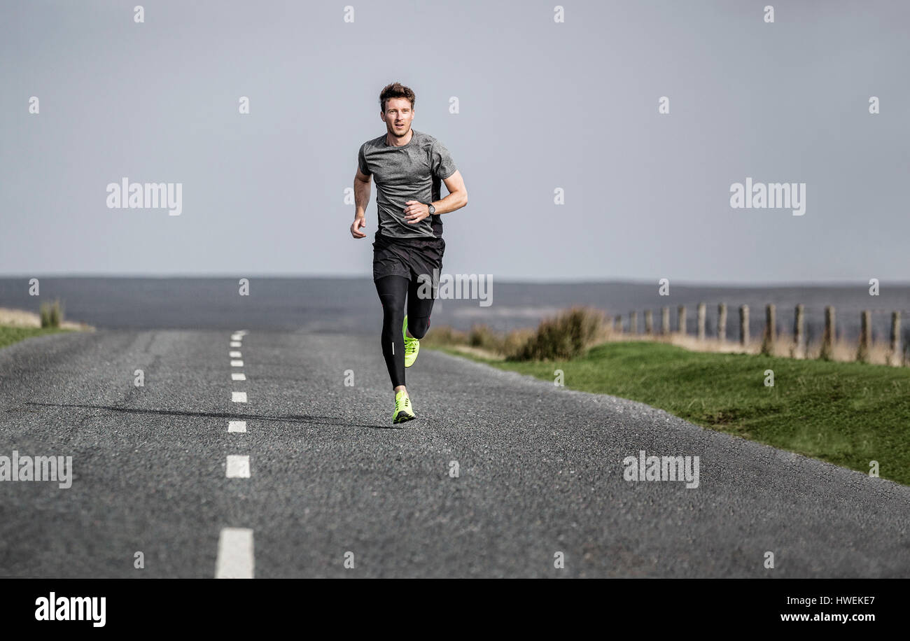 Male runner running along rural moorland road - Stock Image