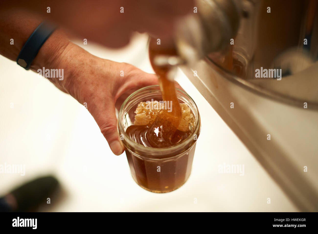 Hands of female beekeeper pouring honey into jar from kitchen vat - Stock Image