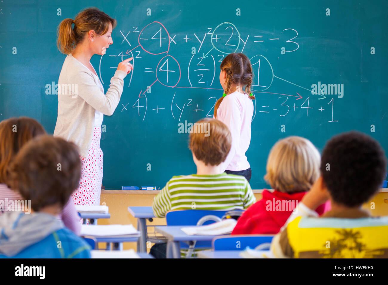 Primary school teacher explaining equation on classroom blackboard - Stock Image