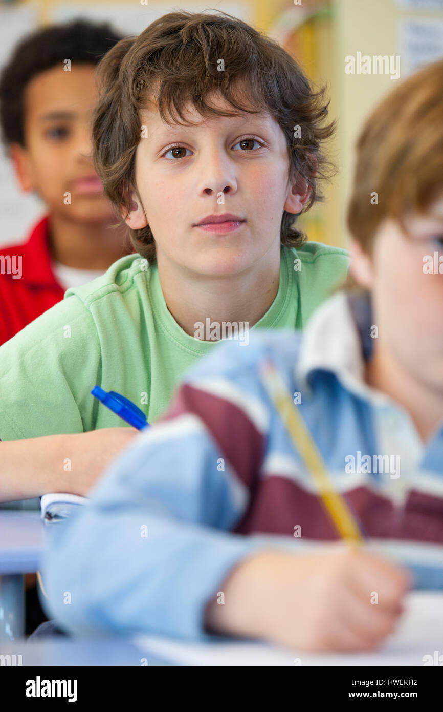 Primary schoolboys writing in classroom - Stock Image