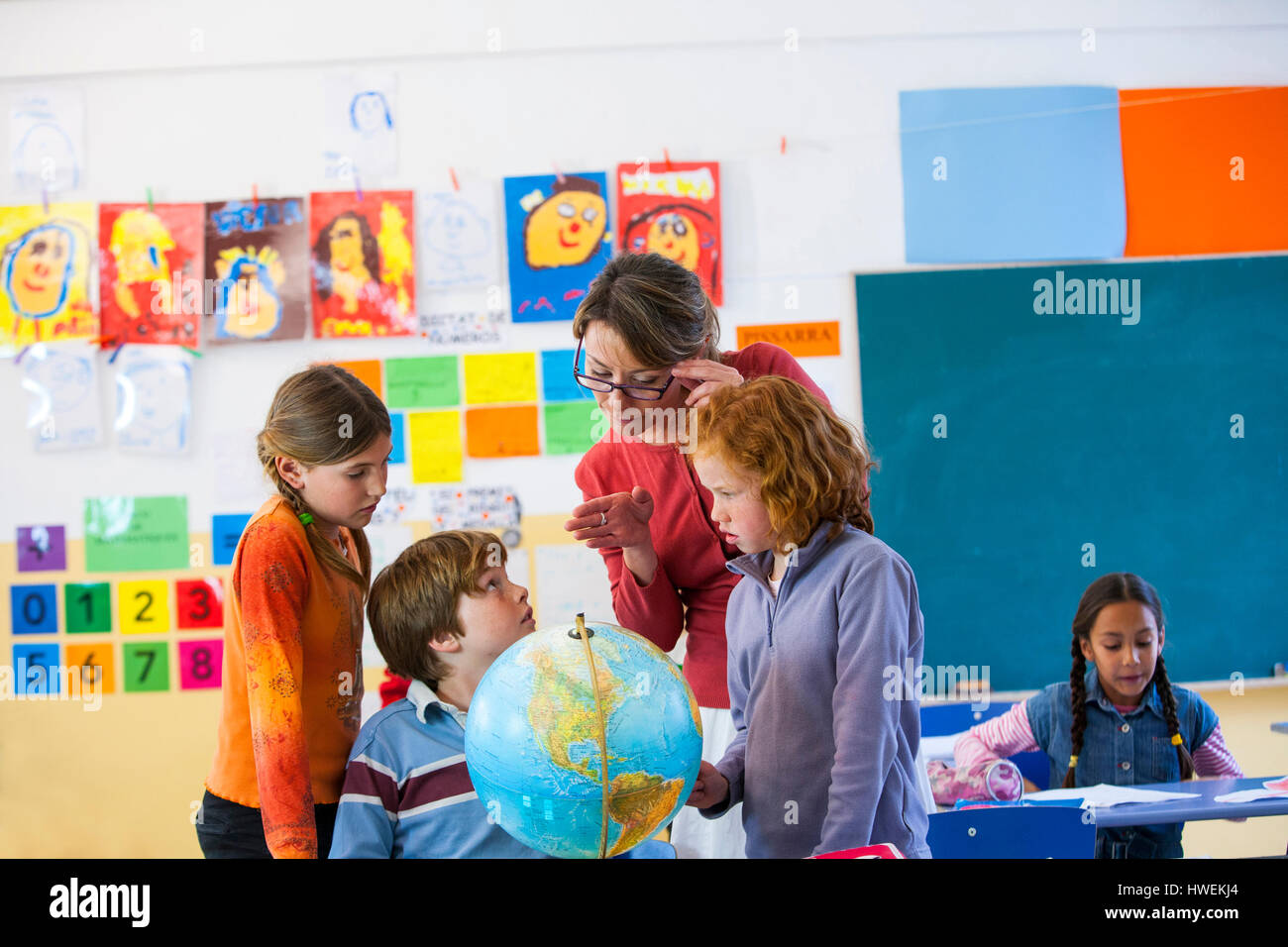 Primary school teacher and schoolchildren looking at globe in classroom Stock Photo