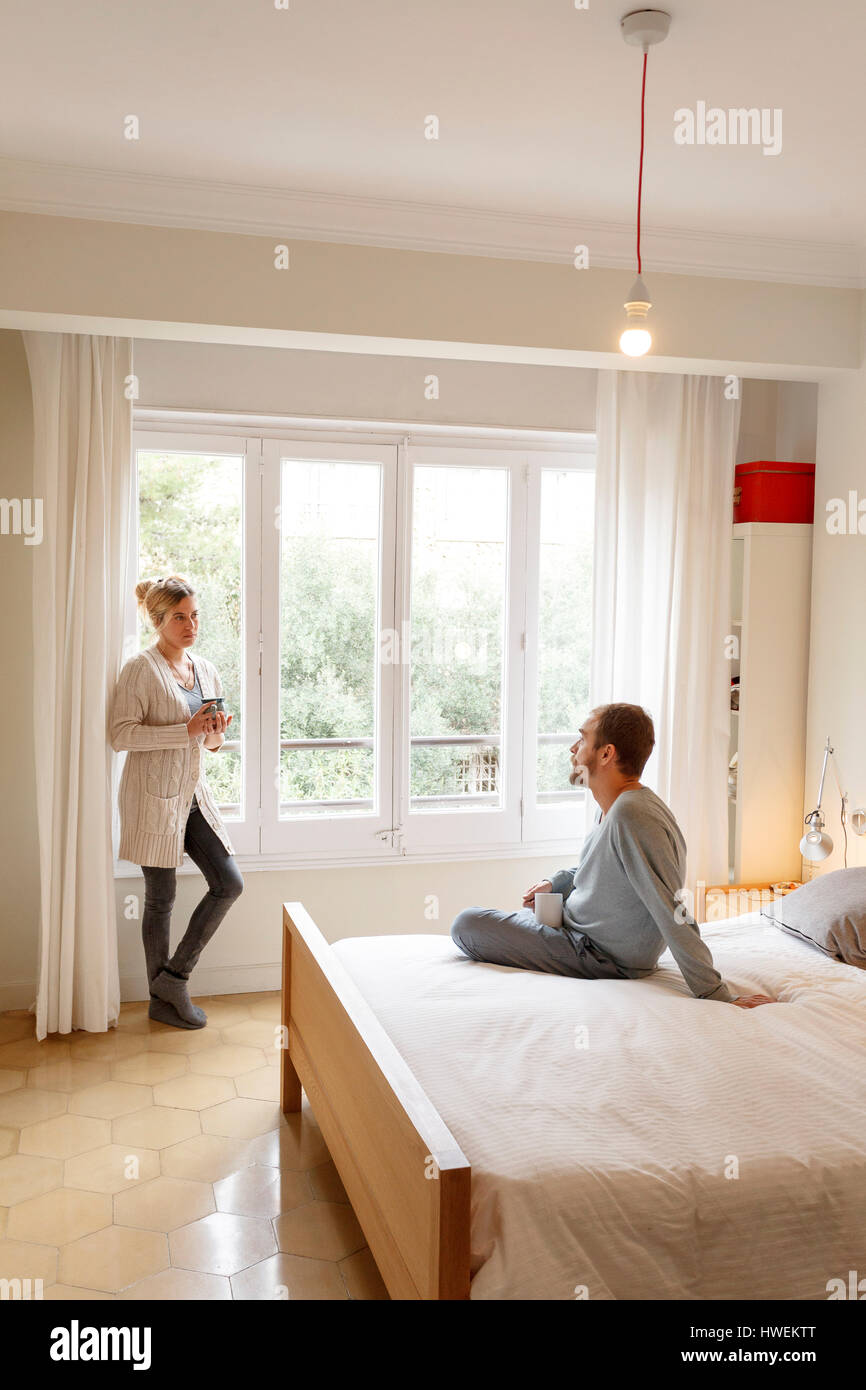 Mid adult couple in bedroom, having disagreement - Stock Image