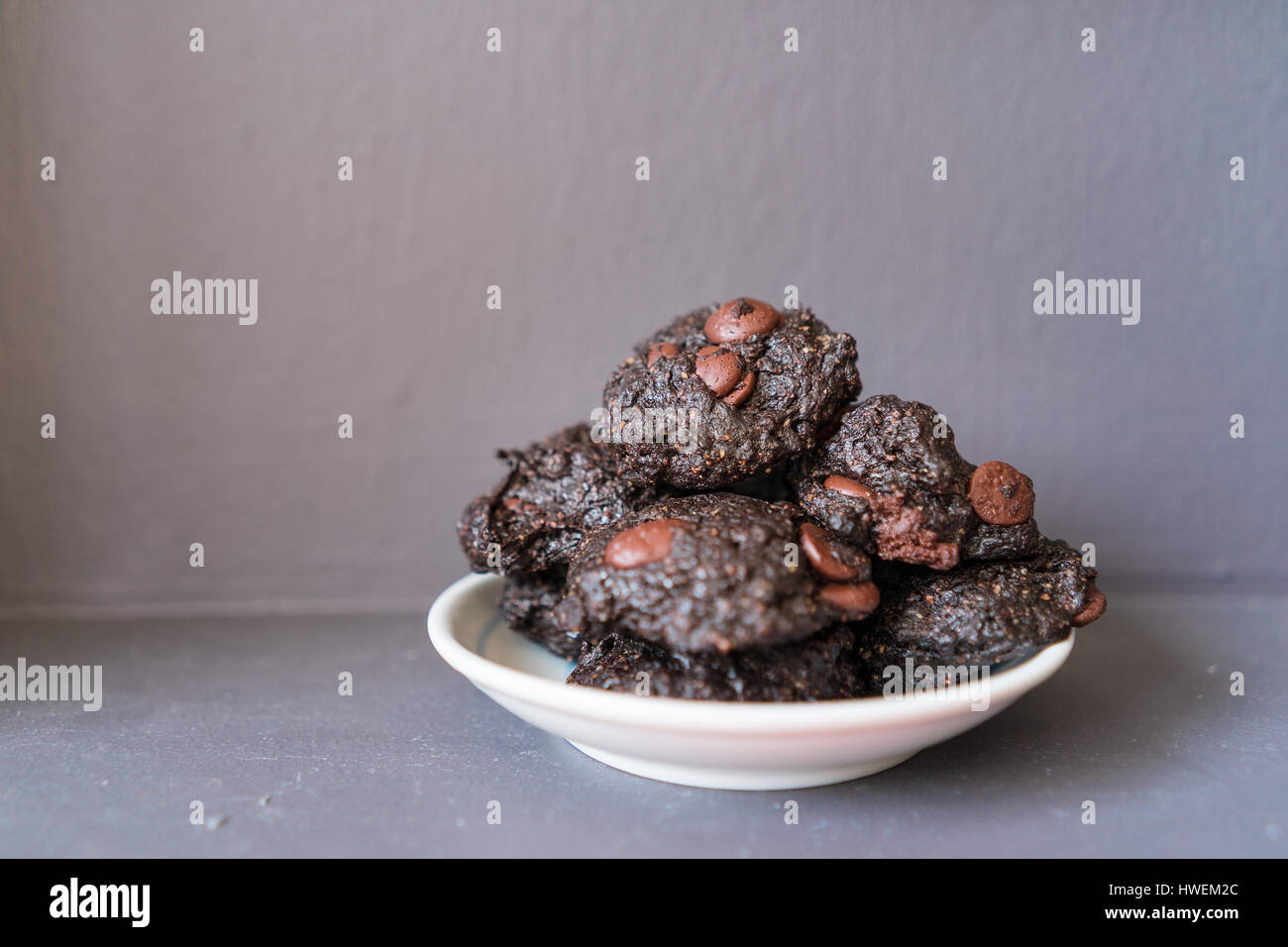 Stack of Vegan chocolate brownie cookie on white round plate - Stock Image