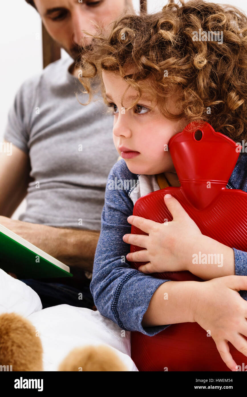 Girl hugging hot water bottle while father reads storybook in bed - Stock Image