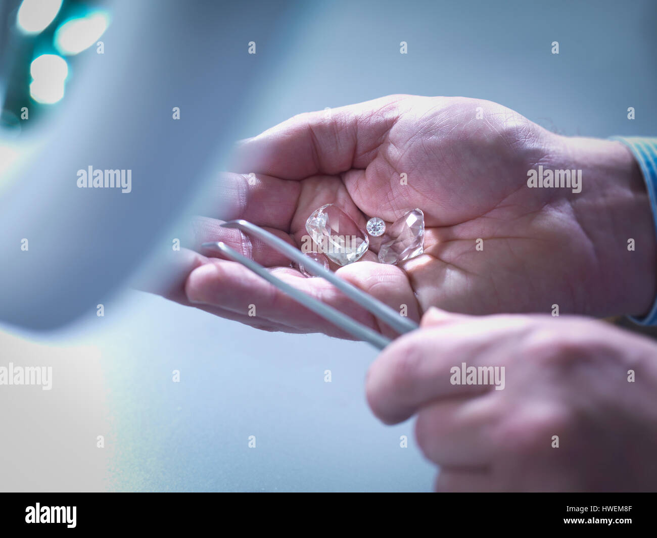 Jeweller inspecting replica diamonds in hand - Stock Image
