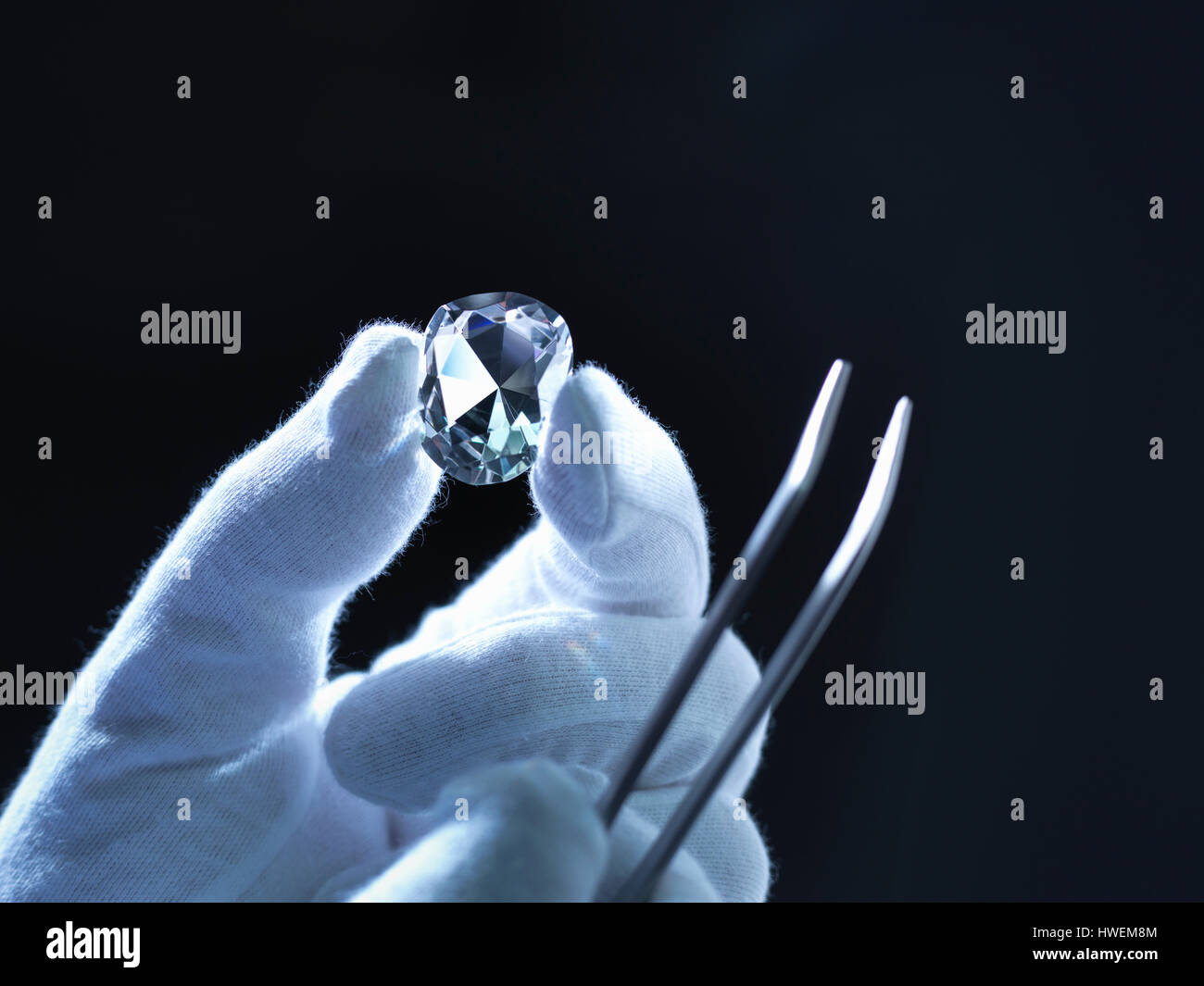 Jeweller inspecting replica diamonds with gloved hand - Stock Image