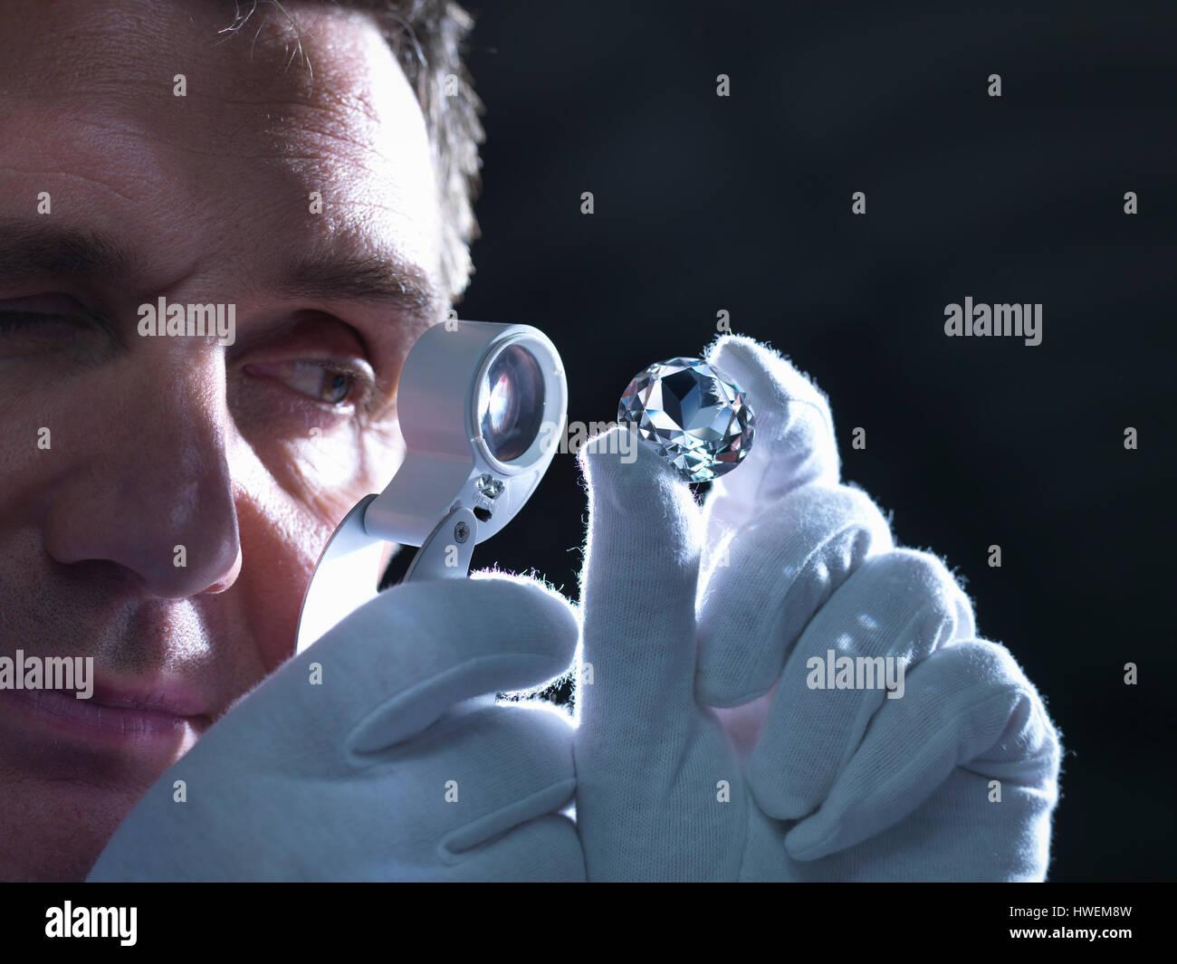 Jeweller inspecting replica diamonds with loupe - Stock Image