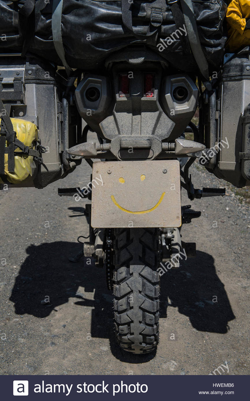 Heavily packed touring motorbike on dirt road, smile drawn on dirty number plate, close-up, Tierra del Fuego, Argentina - Stock Image