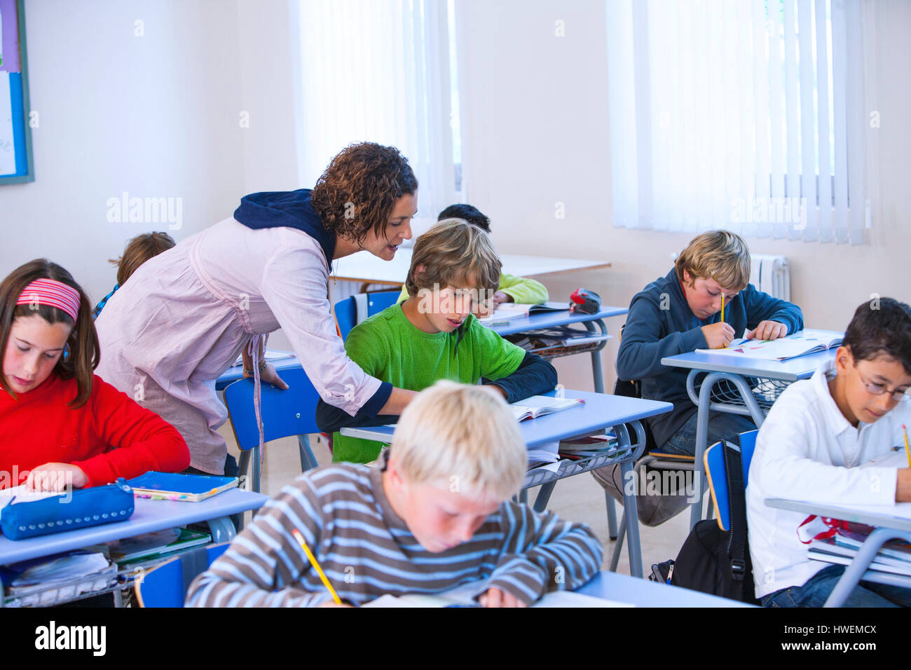 Teacher helping boy with problem in classroom - Stock Image