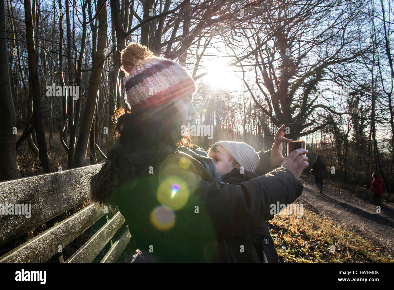 Mother sitting on bench with baby boy, taking selfie with smartphone - Stock Image