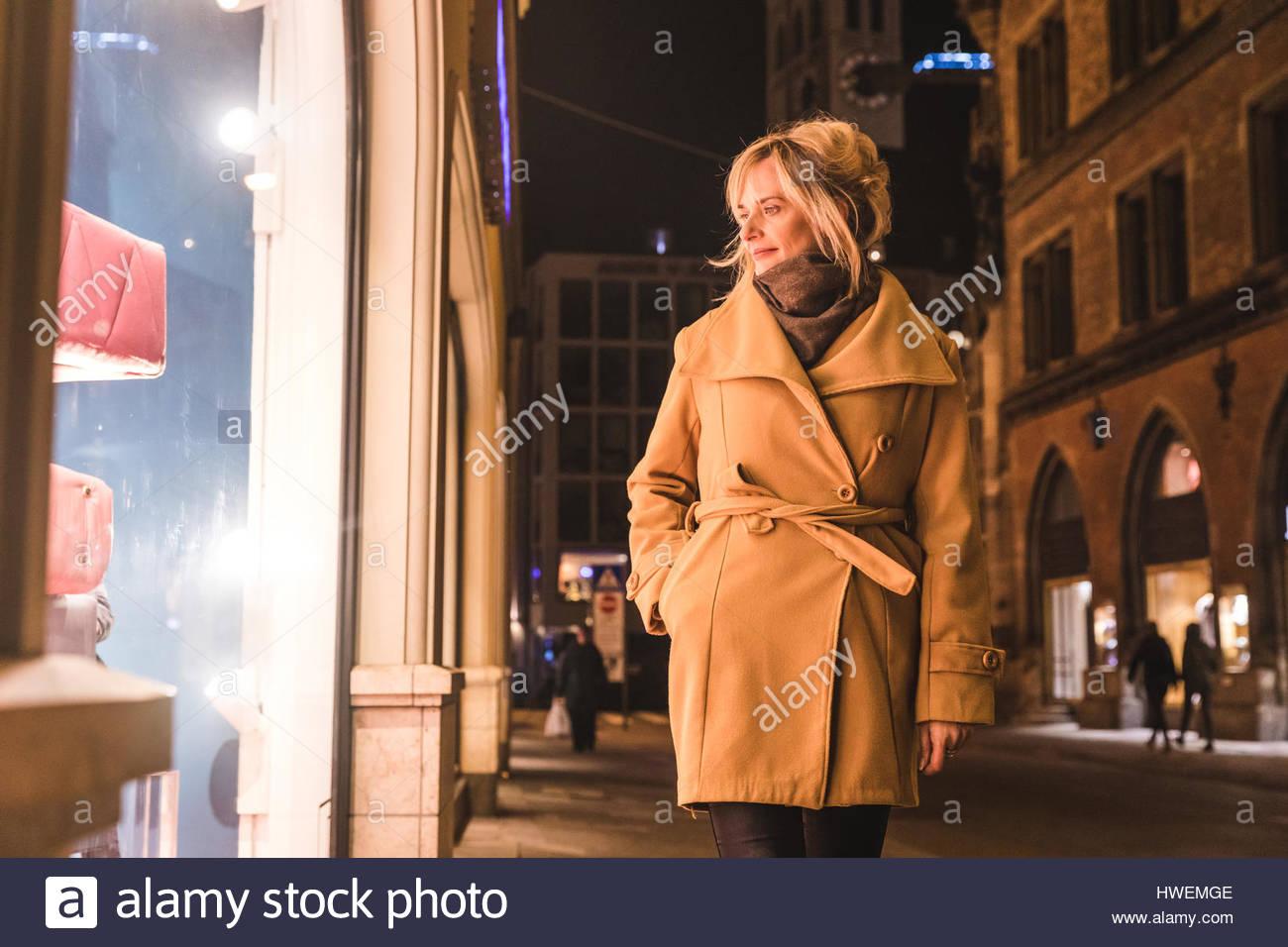 Mature woman window shopping at night, Munich, Germany - Stock Image