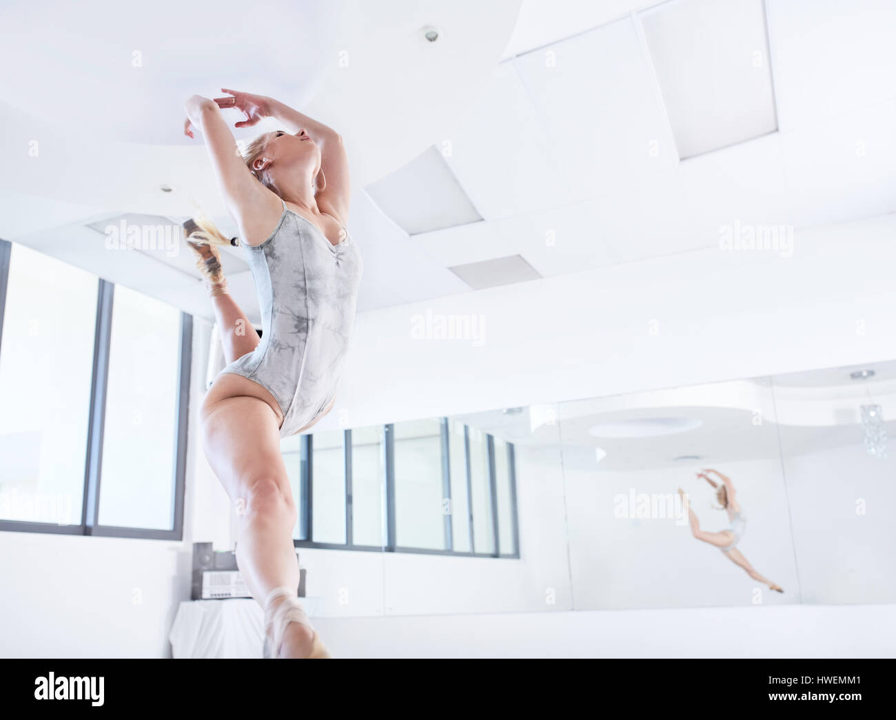Young female ballet dancer leaping in dance studio - Stock Image