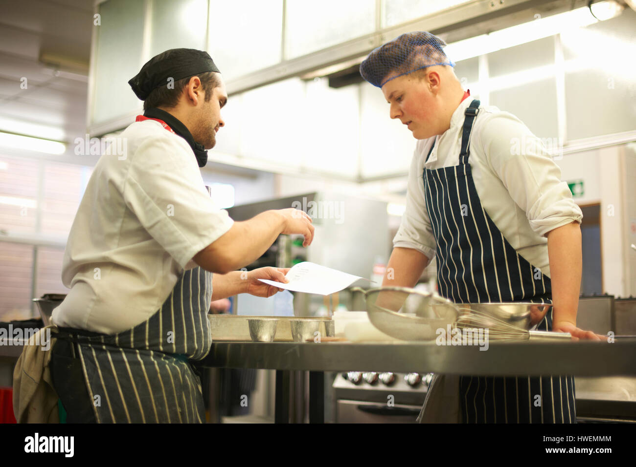 Chef lecturer explaining recipe to teenage catering student in college kitchen - Stock Image