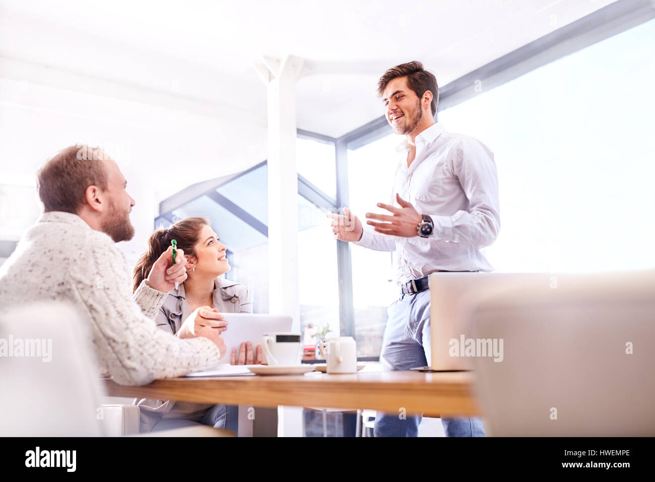 Young businessman making presentation to business team in office - Stock Image