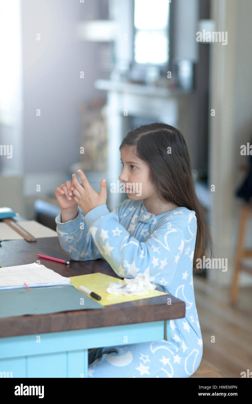 Girl doing homework and counting on fingers at kitchen table Stock ...