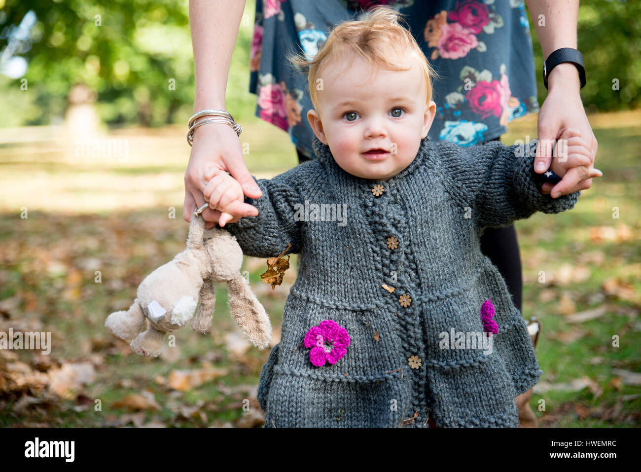 Portrait of baby girl holding mother's hands and toddling in park - Stock Image