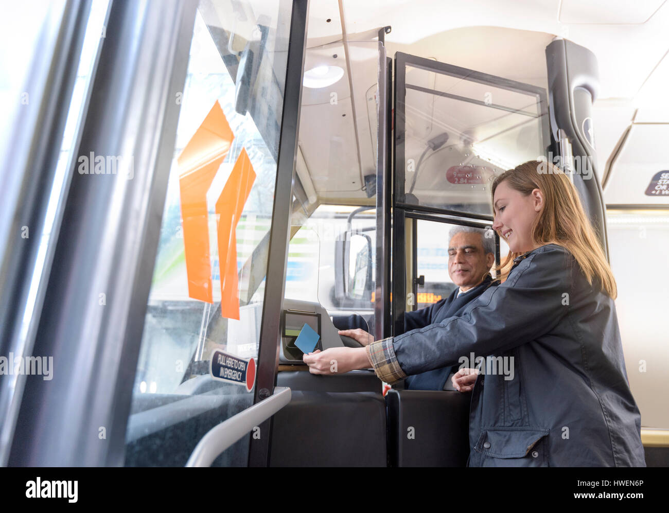 Bus driver with passenger swiping travel card on electric bus - Stock Image