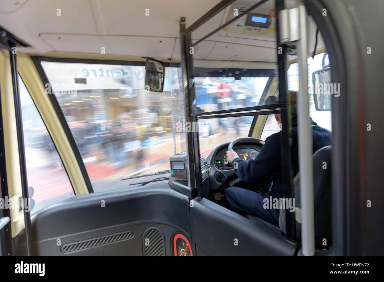 Bus driver driving electric bus in traffic - Stock Image