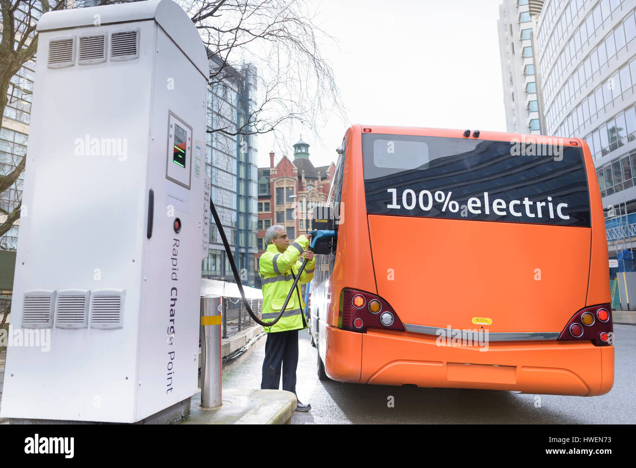 Bus driver charging electric bus at charging station - Stock Image