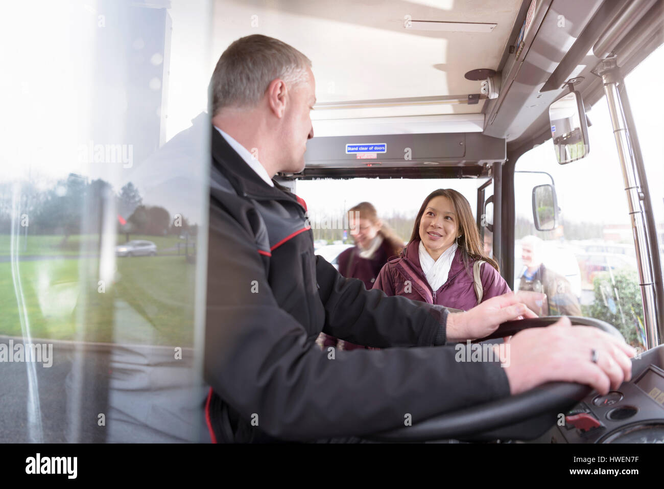 Bus driver with passengers boarding electric bus - Stock Image