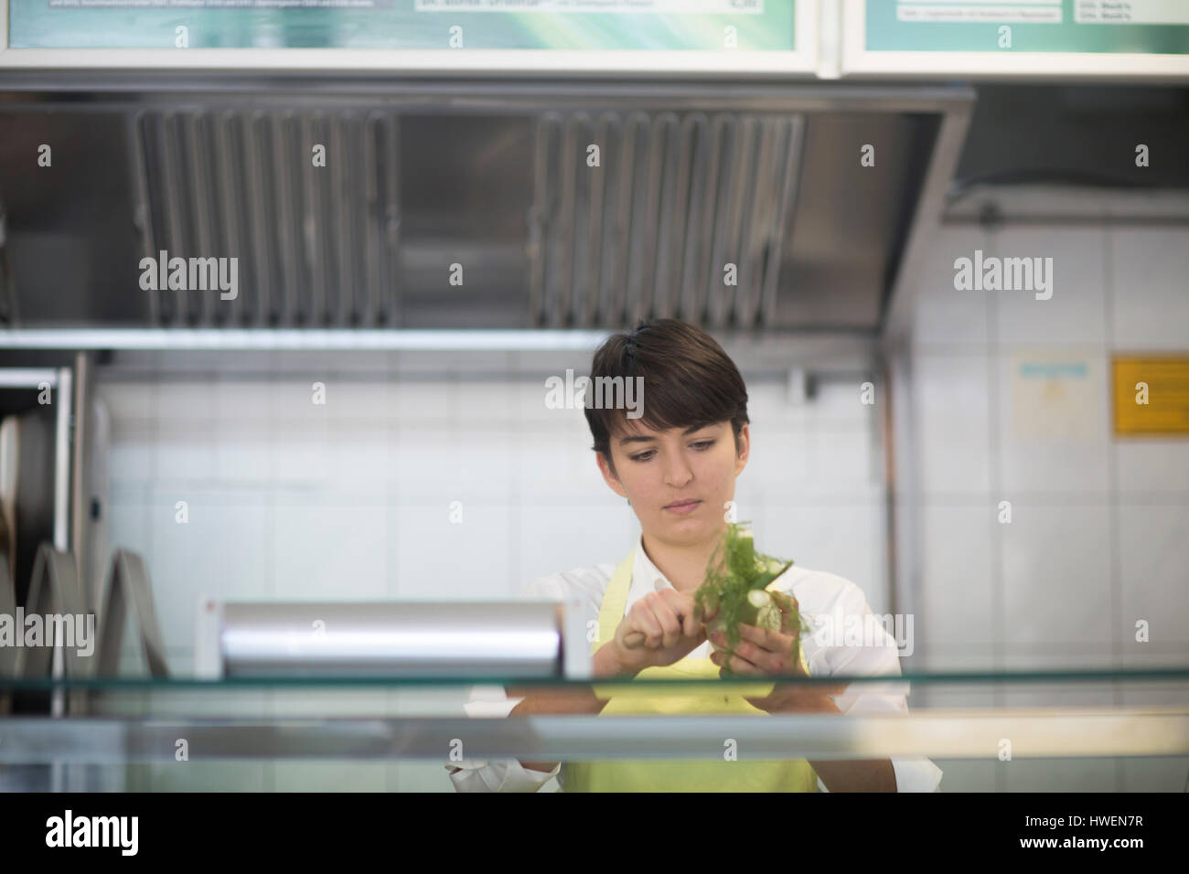 Young woman preparing food in fast food shop - Stock Image