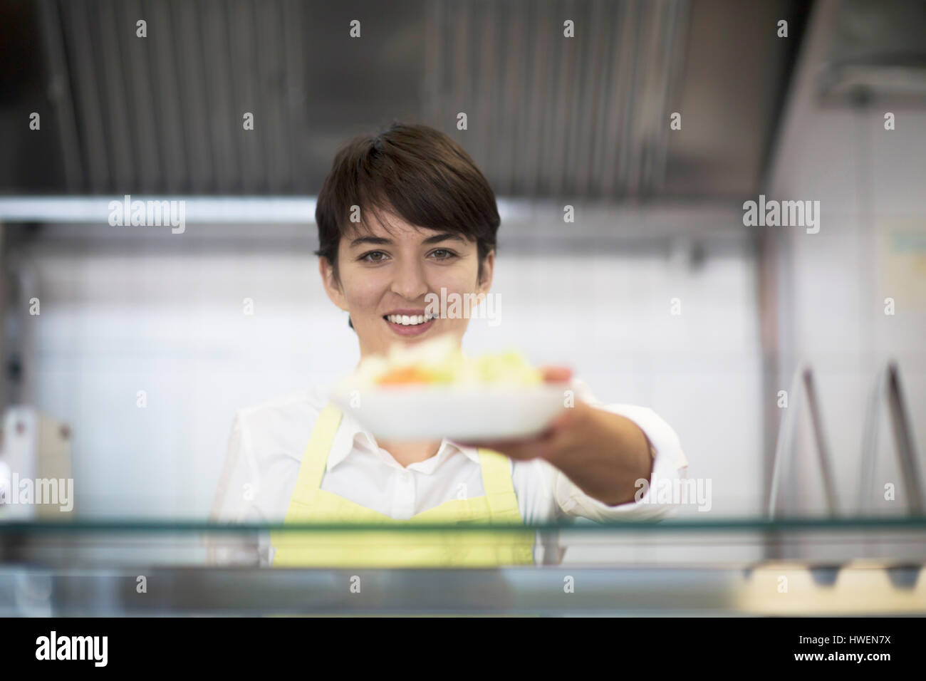 Young woman handing food to customer, in fast food shop - Stock Image