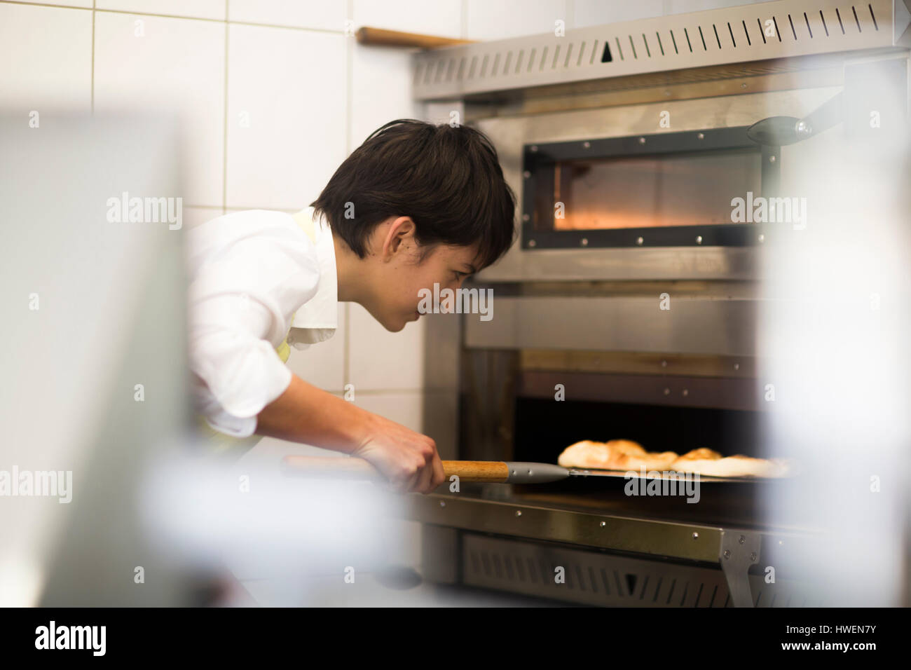 Young woman cooking food in fast food shop - Stock Image