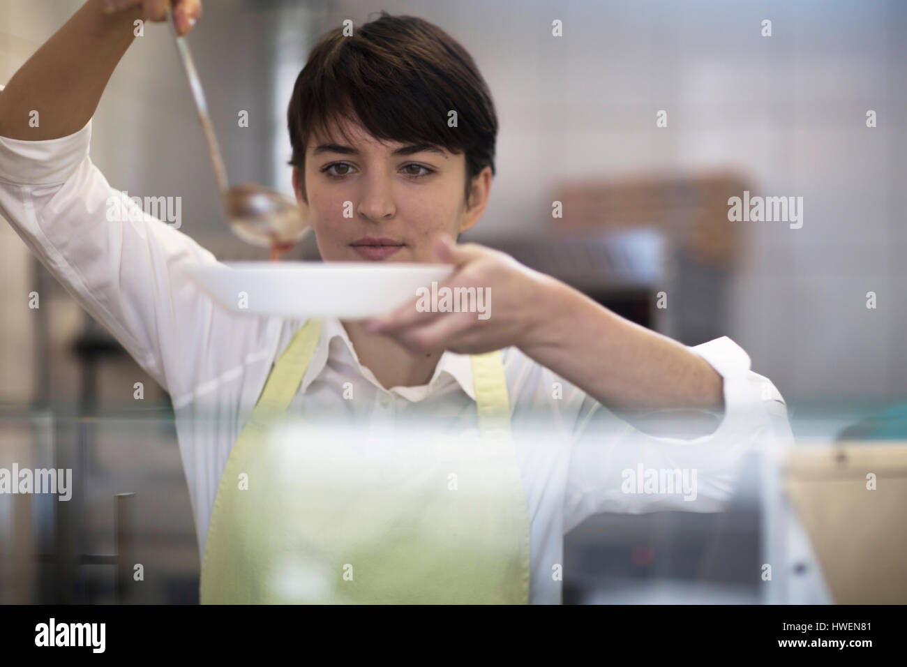 Young woman spooning food into bowl in fast food shop - Stock Image