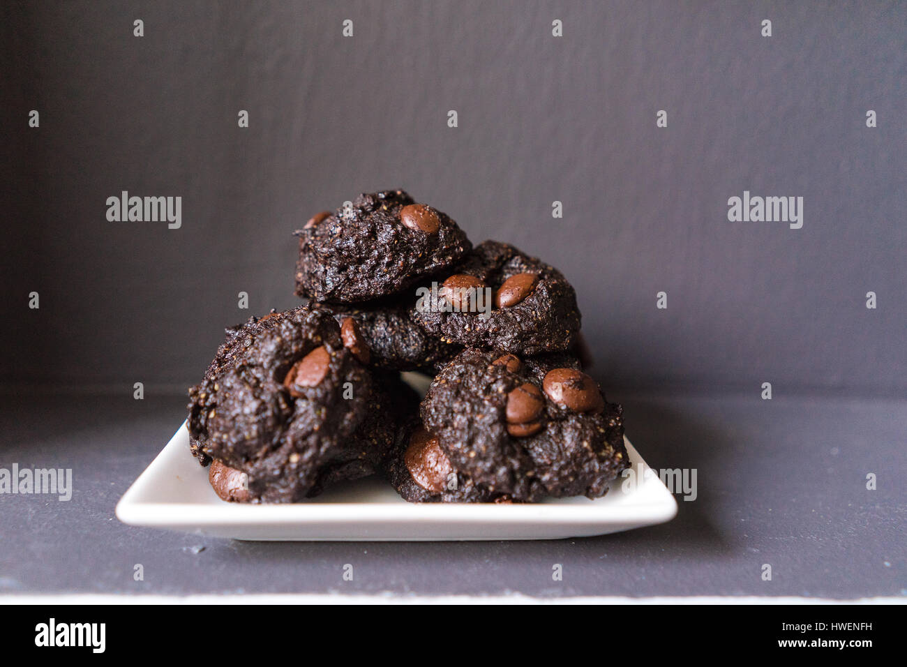Stack of Vegan chocolate brownie cookie on white square plate - Stock Image