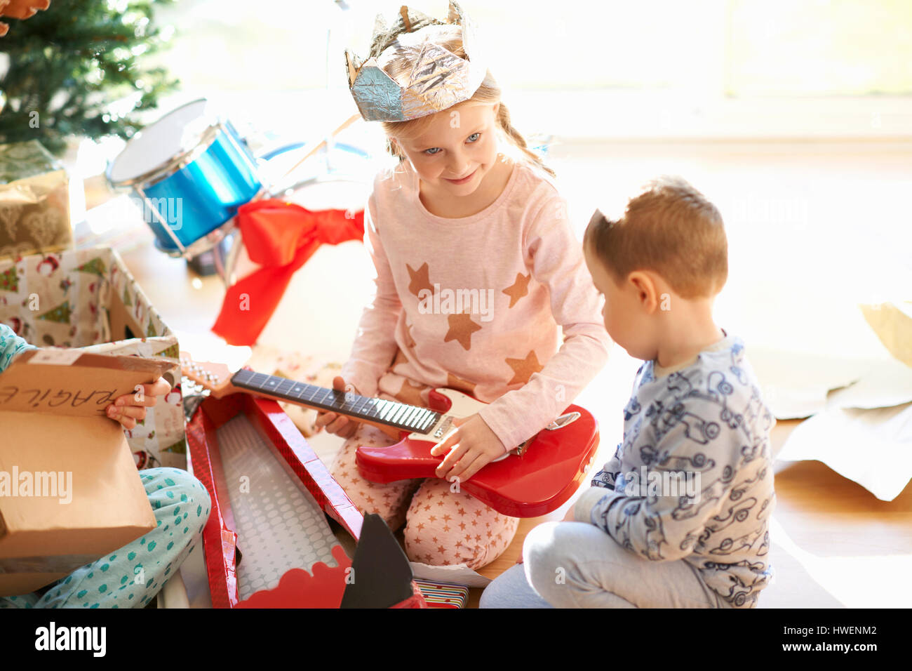 Girl and brother playing with toy guitar on christmas day - Stock Image