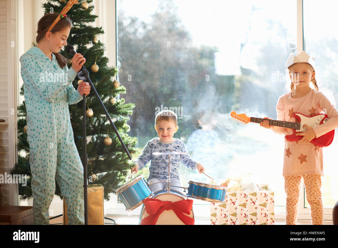Boy and sisters playing toy drum kit and guitar on christmas day - Stock Image