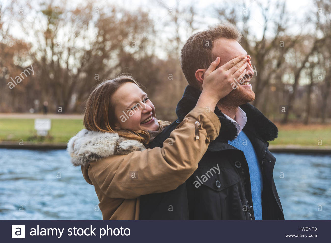 Young woman covering boyfriend's eyes on park riverside - Stock Image