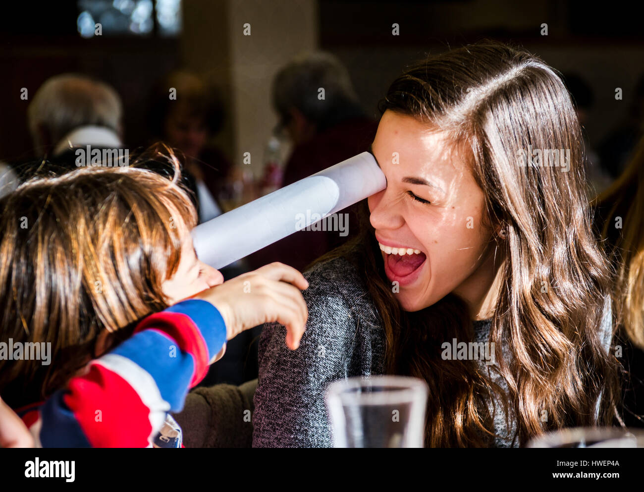 Young woman and boy looking at each other through rolled paper in cafe - Stock Image