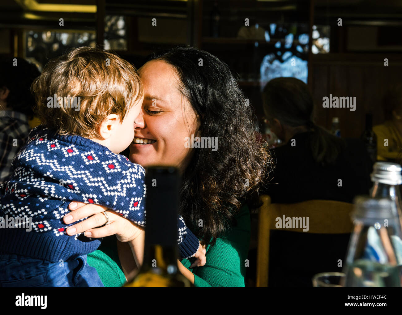 Mature woman face to face with baby son in cafe - Stock Image