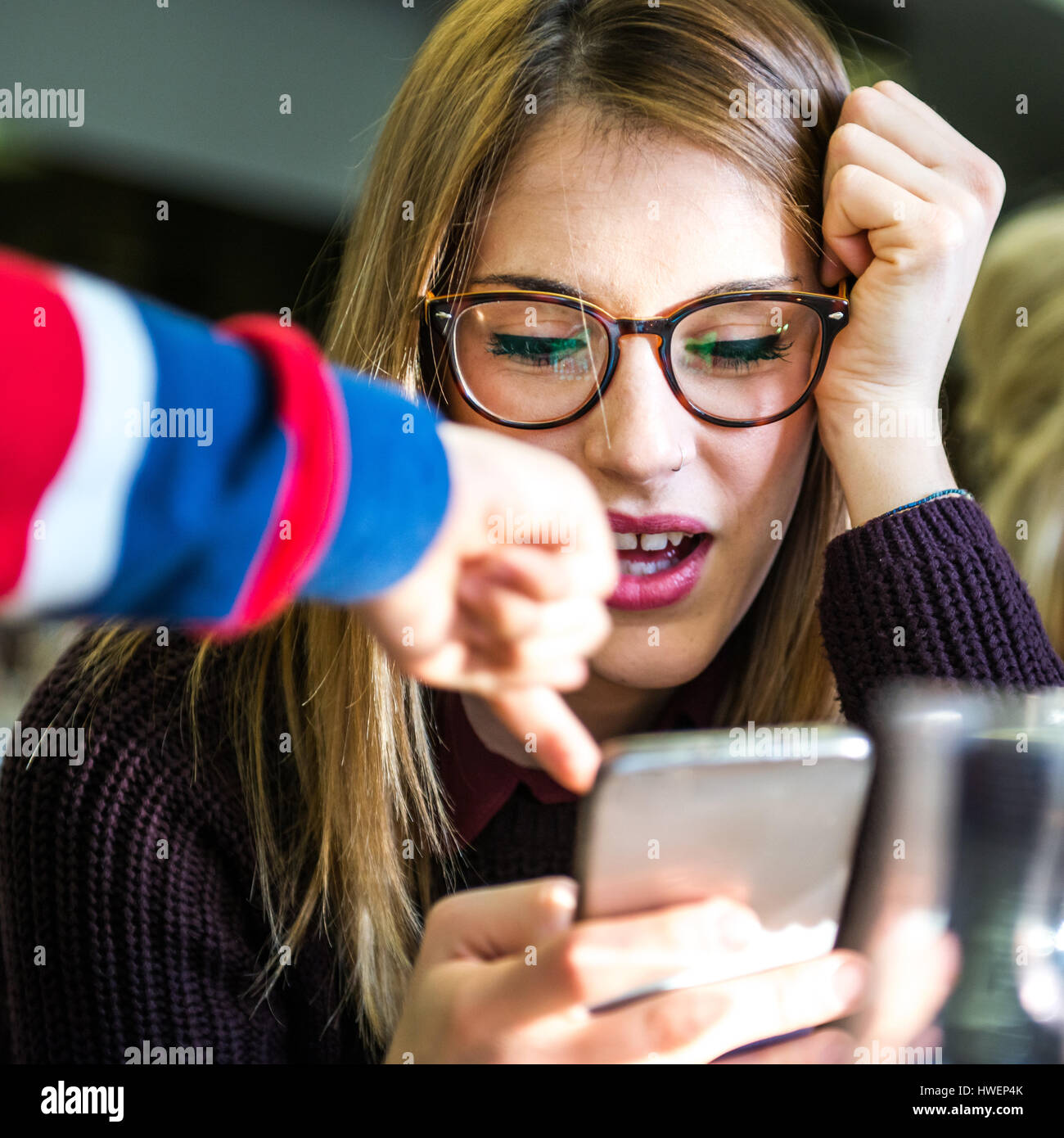 Young woman with boy's hand pointing at smartphone in cafe - Stock Image