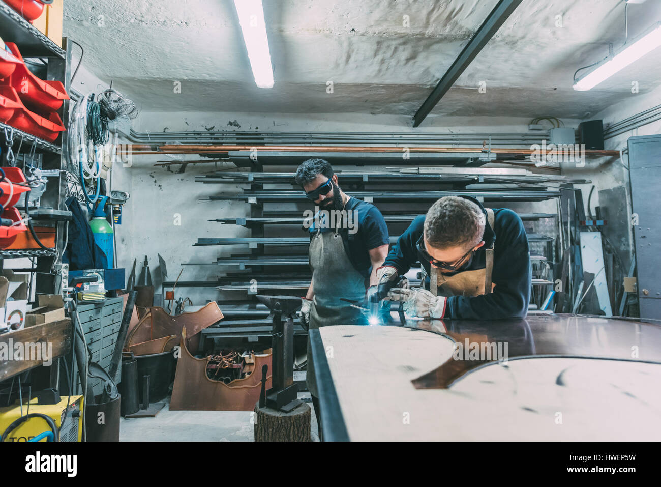 Metalworker cutting copper with welding torch in forge workshop - Stock Image